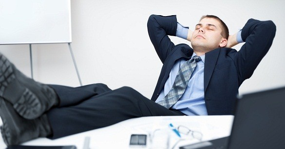Tired businessman sleeping on chair in office with his legs on t